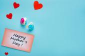 Horní pohled na šťastné matky den nápis na kartě s dudlíky a papírové srdce na modrém pozadí