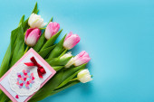 Top view of greeting card on tulips on blue surface