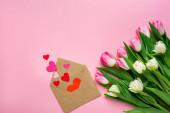 Top kilátás boríték papír szív közelében csokor tulipán rózsaszín felületen