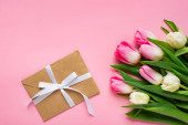 Horní pohled na obálku s lukem a kyticí tulipánů na růžovém povrchu