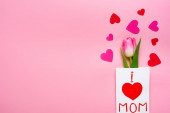 Fotografie Top view of greeting card with i love mom lettering, tulip and paper hearts on pink background