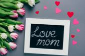 Horní pohled na tabuli s láskou maminka písmo, papírové srdce a tulipány na šedém pozadí
