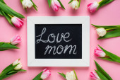 Top view of tulips around chalkboard with love mom lettering on pink background