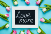 Top view of tulips around chalkboard with love mom lettering on blue background