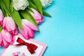 Zavřít pohled na kytici tulipánů v blízkosti blahopřání na modrém povrchu