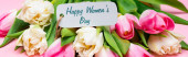 Panoramic shot of happy womens day lettering on paper label on bouquet of tulips on pink background