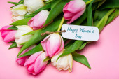 Bouquet of tulips and paper label with happy womens day lettering on pink surface
