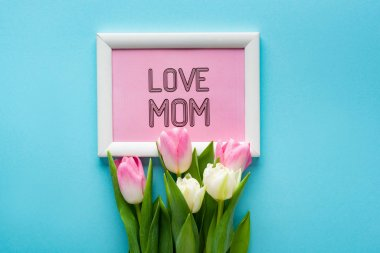 Top view of tulips on frame with i love mom lettering on blue background stock vector