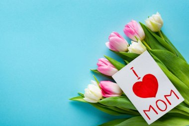 Top view of greeting card with i love mom lettering on bouquet of tulips on blue background
