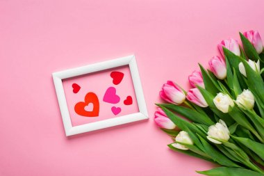 Top view of paper hearts in frame near bouquet of tulips on pink background