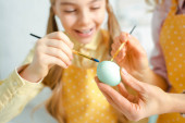 selective focus of happy daughter and mother painting easter egg