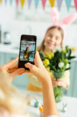 Photo selective focus of mother taking photo of cute daughter in bunny ears with tulips