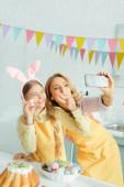 Fotografie selektivní zaměření šťastné matky a dcery v králičí uši ukazující znamení míru při užívání selfie s malovaným velikonočním vejcem