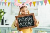 fröhliches Kind mit Hasenohren blickt auf Tafel mit fröhlichem Osterschriftzug