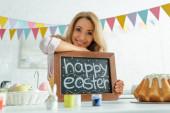 selektivní zaměření veselé ženy držící tabuli se šťastnými velikonočními písmeny