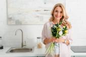 šťastná žena drží kytici tulipánů a dívá se do kamery