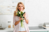 happy woman holding bouquet of tulips at home