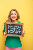 Lächelnde Frau mit Kreidetafel mit fröhlichem Osteraufdruck auf gelbem Grund