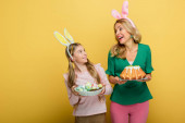 happy mother with bunny ears holding easter cake near cute daughter with painted chicken eggs isolated on yellow