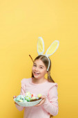 happy kid with bunny ears holding easter eggs in basket isolated on yellow