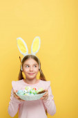 cheerful kid with bunny ears holding easter eggs in basket and looking away isolated on yellow