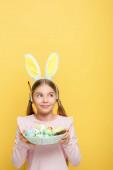 vidám kölyök nyuszifül tartja húsvéti tojás kosárban, és nézte félre elszigetelt sárga