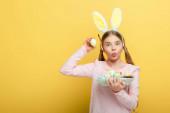 šokované dítě s králičí uši při pohledu na kameru a držení velikonoční vejce izolované na žluté