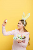 cute kid with bunny ears looking at easter egg isolated on yellow