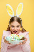 excited child with bunny ears looking at easter eggs in basket isolated on yellow