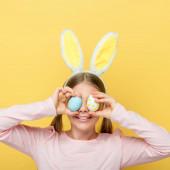 vidám gyermek nyuszifül borító szem húsvéti tojás izolált sárga