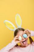 Kind mit Hasenohren, die die Zunge herausstrecken und die Augen mit Ostereiern bedecken