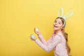 positive child with bunny ears holding painted easter eggs isolated on yellow