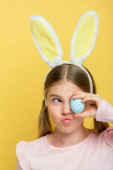 funny kid with bunny ears covering eye with dotted easter eggs isolated on yellow