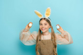 positive kid with bunny ears holding painted easter eggs on blue