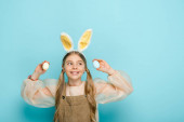 positive child with bunny ears holding painted easter eggs on blue