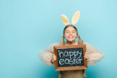 Fotografie Lächelndes Kind mit Hasenohren mit Kreidetafel mit fröhlichem Osteraufdruck auf blauem Grund