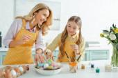 Glückliche Mutter schaut Tochter beim Ostereierholen zu