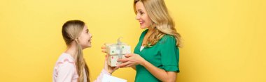 panoramic shot of happy kid giving present to mother isolated on yellow
