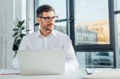 professional translator in eyeglasses working with laptop