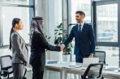 profesionální multietničtí podnikatelé potřásající si rukou při setkání s překladatelem v kanceláři