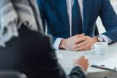 Fotografie abgeschnittene Ansicht von Geschäftsleuten, die sich mit Kaffeetassen im Büro treffen