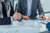 cropped view of business partners with contract and coffee on meeting in office