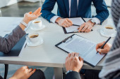 cropped view of professional business partners signing contract on meeting in office with coffee cups