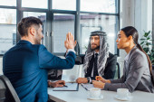 Photo positive multicultural business partners giving highfive on meeting with translator in office