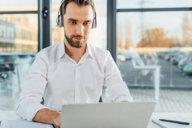 male translator working online with headphones and laptop in office