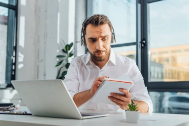professional translator writing and working online with headphones and laptop in office