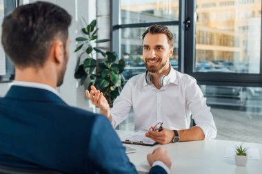 cheerful male translator working with businessman in modern office