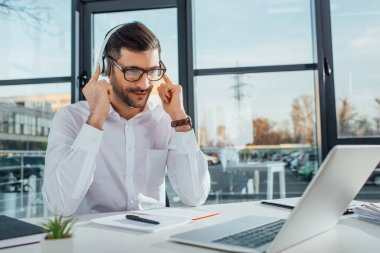 professional male translator in eyeglasses working online with headphones and laptop