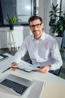 Smiling male translator working with documents and laptop in office stock vector