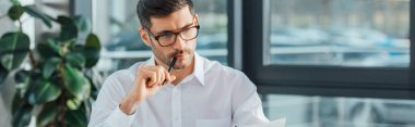 panoramic shot of thoughtful translator working with documents in office